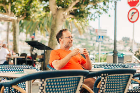 Happy middle age man relaxing in summer outdoor cafe, holding cup of coffee, wearing orange t-shirt and eyeglasses