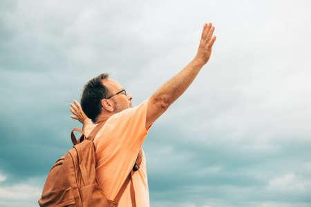Uomo in piedi in cima alla collina, con indosso lo zaino e le braccia aperte