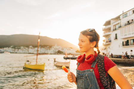Close up portrait of happy teenage girl posing by the sea, wearing backpack and sunglasses