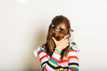 Studio portrait of young girl fooling around, hiding behind, hair, acting silly, time for haircut, hair completely covering the face with glasses over Standard-Bild