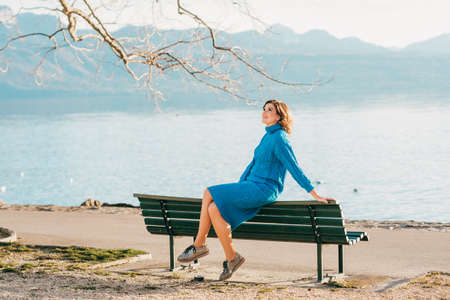 Outdoor portrait of young woman resting on the bench by the lake in early spring, wearing blue knitted pullover dress 免版税图像