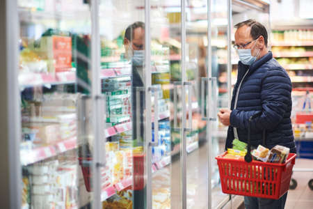Middle age man buying food in grocery store, wearing medical mask Foto de archivo