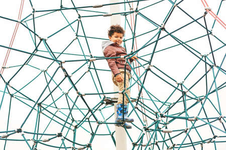 Little kid boy on the top of climbing net, playground activities for children
