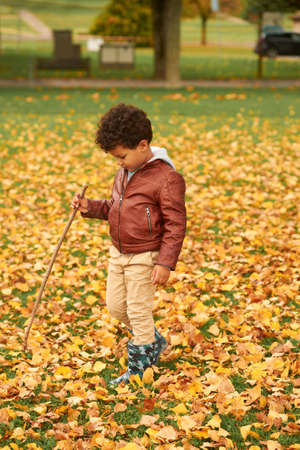 Outdoor autumn portrait of cute african boy, wearing brown leather jacket, child having fun in park