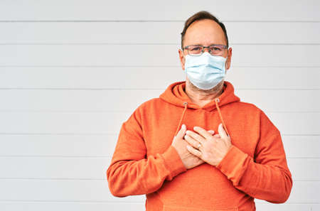 Middle age man wearing medical facial mask, holding hands on chest