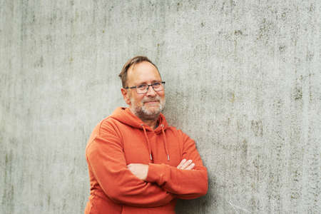 Outdoor portrait of handsome middle age man posing against grey urban wall, wearing bright orange hoody and eyeglasses Imagens