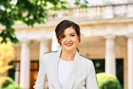 Outdoor portrait of beautiful stylish woman wearing white blazer
