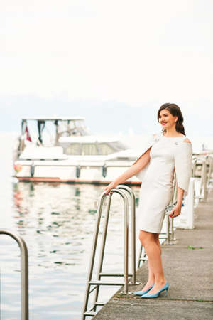 Outdoor fashion portrait of beautiful stylish woman wearing white dress, resting by the sea