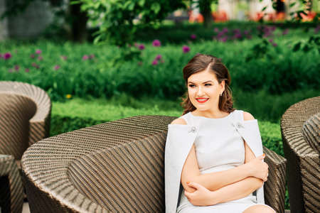 Outdoor portrait of beautiful stylish woman wearing white dress