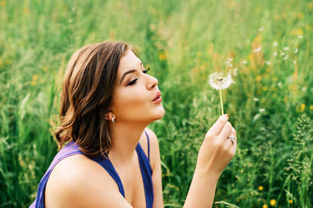 Summer portrait of happy young woman relaxing in wild flower field, playing with dandelion Фото со стока