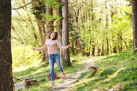 Fit young woman hiking in morning forest, girl full of energy, jumping happily