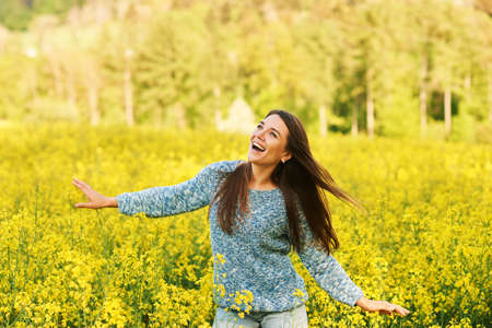 Spring portrait of happy young woman posing in colza field Stok Fotoğraf