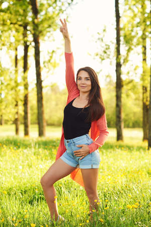 Outdoor portrait of happy young woman enjoying nice day in summer park