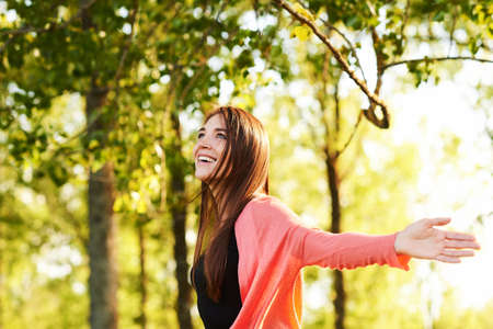 Outdoor portrait of beautiful young woman with brown hair, relaxing in nature
