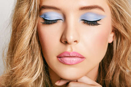 Close up portrait of young female model with bright makeup, eyes, closed, pink lip gloss and blue eyedhadows
