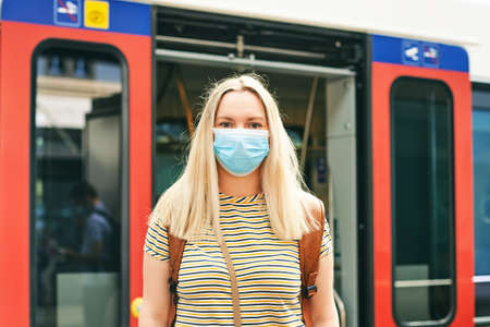 Young woman wearing face mask and backpack, standing at the train station, metro or bus station 版權商用圖片