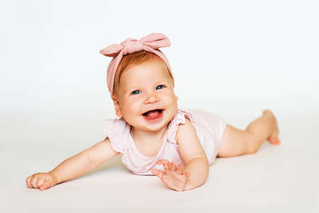 Portrait of adorable red-haired baby lying on belly, white background, wearing pink body and headband
