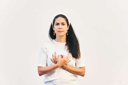 Portrait of woman holding gyan mudra next to heart, hand position from Kundalini yoga meditation Love is Love. This meditation removes any duality between love in your life and love in your soul Stock Photo