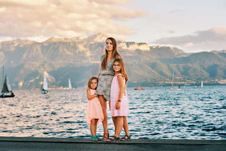 Outdoor portrait of young mother with 2 little daughters, nice summer day by the lake