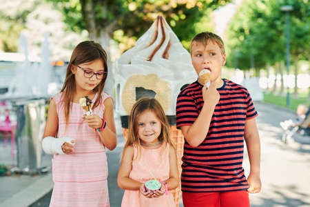 Group of 3 funny kids eating ice cream outdoors on a nice sunny day