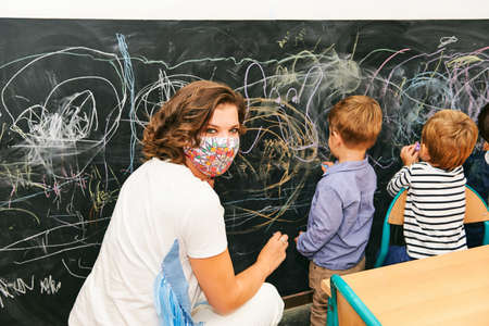 Art classroom in kindergarten, young teacher drawing with children on chalk wall, wearing facemask