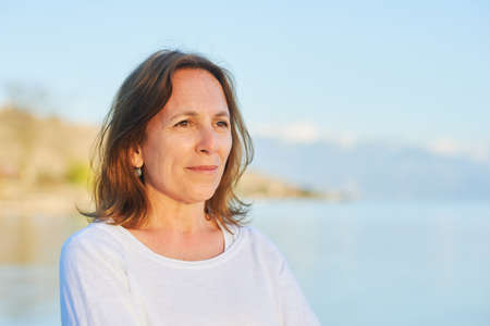 Outdoor close up portrait of 50 year old woman resting by the lake Stock Photo