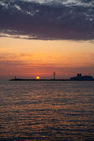 Beautiful night sky behind the shining lighthouse. Sunset in the sea and a small lighthouse 写真素材