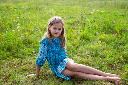 portrait of a cute little girl lying in a meadow. Beautiful girl with curly blonde hair in a dress and feet