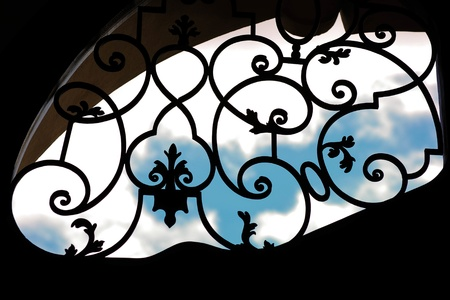Wrought iron grating over blue sky photo