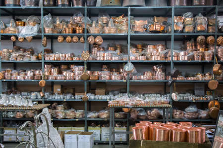 Copper kitchenware on the shelves of the shop.