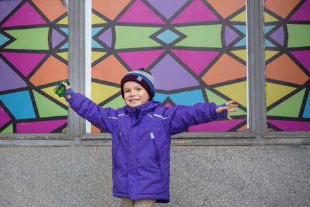 Charming smiling boy 4-5 years old in a purple sports jacket and a hat near a multi-colored wall. Spreading his arms looks at the camera. emotion of joy, victory, jubilation Imagens