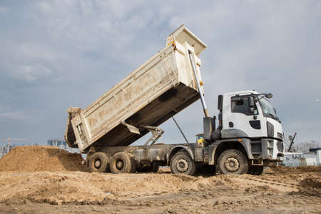dump truck at work on a construction site. The process of transporting and unloading soil on a construction machine. Excavation