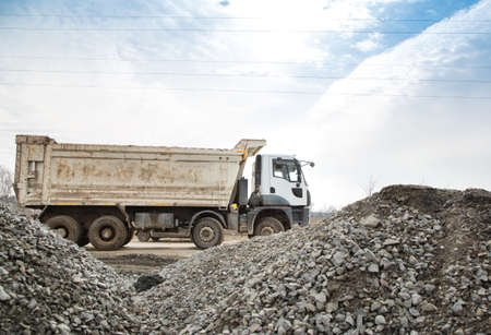 dump truck rides on a construction site. Large piles of rubble in the foreground.