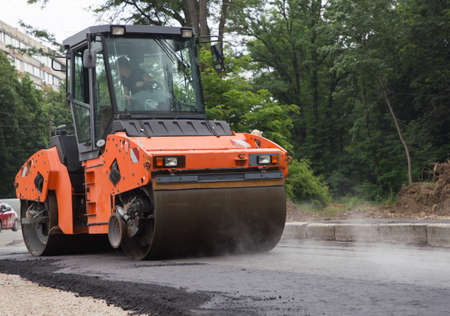 large orange roller in the process of rolling hot asphalt. paving works. Improvement of the city. Equipment for road construction and repair