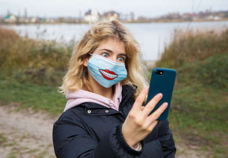 cute young woman, teen girl in medical mask with drawn funny smile. Takes selfie photo, communicates online. The emotion of amazement, horror. Big round eyes. quarantine, pandemic. Use masks 版權商用圖片
