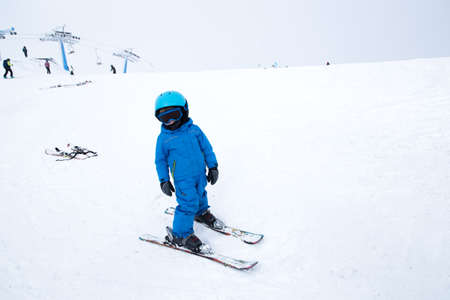 toddler in helmet, glasses, skis and blue overalls stands on snowy mountainside. Children's skiing lesson at ski school. Winter active entertainment for children, sports education. Active childhood