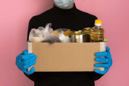 Delivery of a box of food to volunteers during the pandemic. Hands in medical gloves hold the box. Help from volunteers. Self-isolation during the coronavirus period. Delivery service.