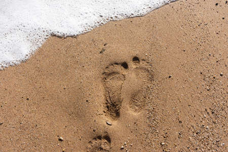 Human footprints on the beach. Top view of the composition of tracks and rolling waves. Sea foam and sand. The concept of summer vacation. Dreams of the sea and summer. Summer holiday.