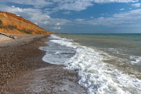 Sea coast with waves and sand. Beautiful summer landscape with stormy sea. Bright sun and blue sky. Clay high banks. The Beaches Of The Crimea 写真素材