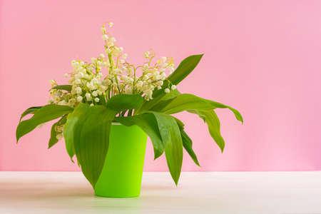 山谷的百合花束在桃红色背景的一块玻璃。春天花的正面布置。美丽和明亮的自然背景。可能鲜花。