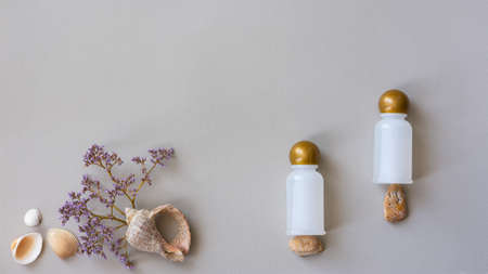 Cosmetic bottles on a gray background. The concept of natural natural cosmetics. Beautiful layout for spas. White bottles for creams, shampoos and shower gels. Natural sea stones and shells. Imagens