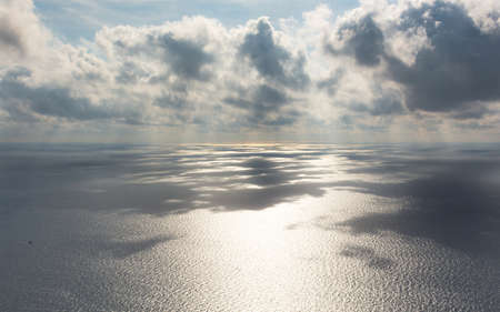 Gray beautiful clouds over the sea. Long panoramic sea autumn view. Low Cumulus clouds and bright sunlight. Shadow of clouds on the surface of the water. Gray steel natural shades of the autumn sea.