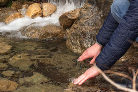 The man lowered his hands into the mountain river. Cold river water. Hand washing on a hike. Natural disasters. A bubbling mountain stream. Men's hands close-up.