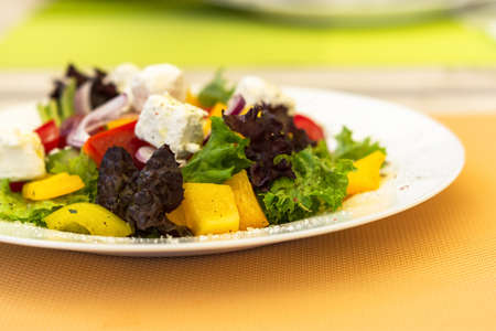 Greek salad on a white plate in a summer cafe. Vegetarian dish. Olives, purple onions and feta cheese. Light snack in a cafe. Summer menu. Natural light.