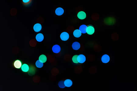 Multi-colored bokeh on a black background. Bright blurry textures of holiday lights. Colorful beautiful Christmas garlands on blurry background. Layout of a greeting card for the New year. Copy space