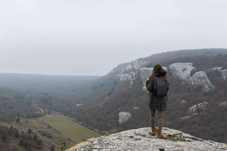 A long-haired young girl with a backpack on the edge of a cliff. A lonely tourist in the autumn in the mountains. Foggy atmospheric landscape. The concept of unity with nature, rest and relaxation.