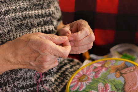 A woman embroiders with a cross. Wrinkled hands close up. An elderly woman holds a hoop and thread with a needle in her hands. Soft focus. The concept of hobby and manual labor. Pleasant home leisure.