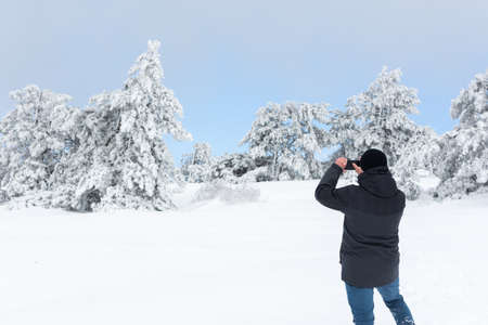 A male tourist takes photos of a winter landscape with snow-covered trees on his phone. Spruce forest in the snow, blue sky. Fabulous winter landscape. The concept of unity with nature. Enjoy the view