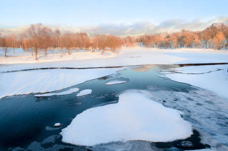 frozen cold pond covered with snow in a park