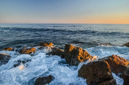 Splashes from the waves bumping against the rocky shore